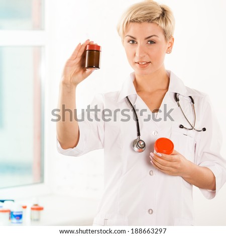 Portrait of a young pharmacist showing pills near the window - stock photo