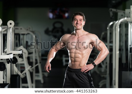 Portrait Of A Young Physically Fit Man Showing His Well Trained Abdominal Muscles - Muscular Athletic Bodybuilder Fitness Model Posing After Exercises - stock photo