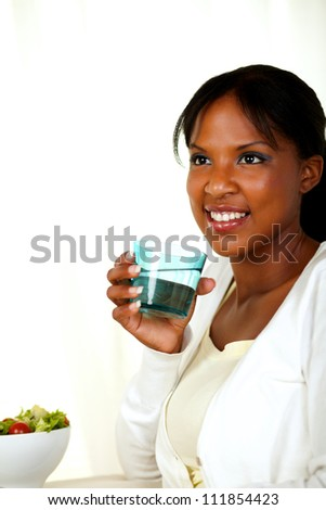 Portrait of a young positive woman smiling and drinking fresh water while looking up - stock photo
