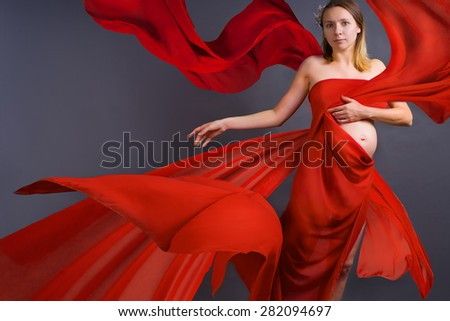 Portrait of a young pregnant woman in red dress with blowing on wind waving fabric, grey background, fashion pregnancy art - stock photo