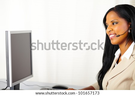 Portrait of a young pretty call center operator at work - stock photo