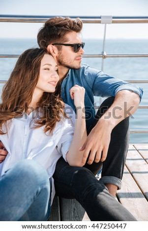 Portrait of a young pretty couple sitting outdoors at the seaside - stock photo