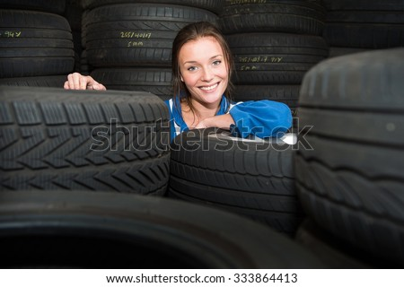 Portrait of a young, pretty, mechanic in a store room, surrounded by tyres with various treads, and purposes - stock photo