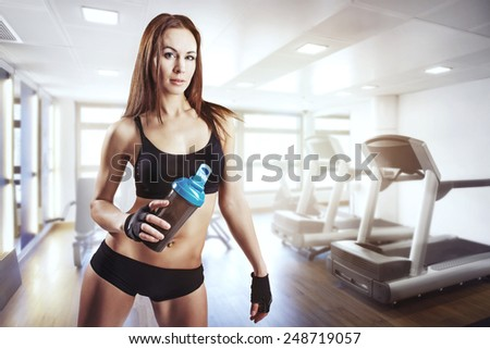 Portrait of a young pretty woman holding shaker - stock photo