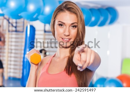 Portrait of a young pretty woman holding weights (dumbbell) and doing fitness indor. Crossfit hall. Gym shot. She is pointing camera. - stock photo