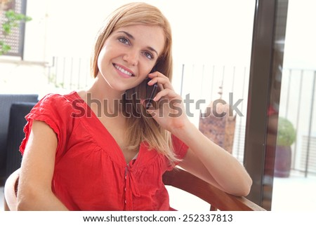 Portrait of a young professional girl sitting smiling at home using a smartphone mobile phone to have a phone conversation next to a large window. Student woman lifestyle and technology, interior. - stock photo