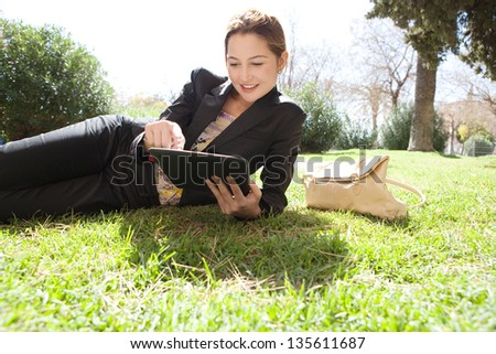 Portrait of a young professional woman laying down on green grass in a city park, using her digital tablet pad with touch screen, smiling. - stock photo