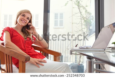 Portrait of a young professional woman sitting in her home office space using smartphone mobile phone to have a call conversation. Student using a laptop computer. Lifestyle and technology, interior. - stock photo