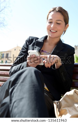 Portrait of a young professional woman sitting on a city park wooden bench while using and dialing on her smartphone, smiling. - stock photo