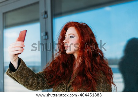 Portrait of a young redhead attractive woman making selfie photo on smartphone for Instagram - stock photo