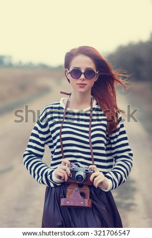 Portrait of a young redhead girl in sunglasses and camera at outdoor in autumn time - stock photo