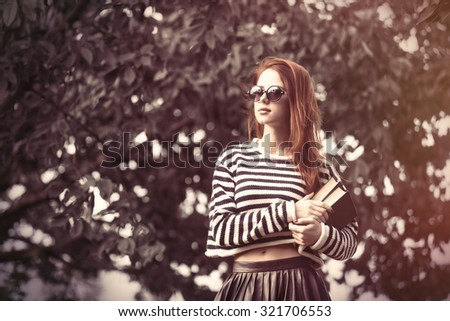 Portrait of a young redhead girl with books at outdoor in autumn time - stock photo