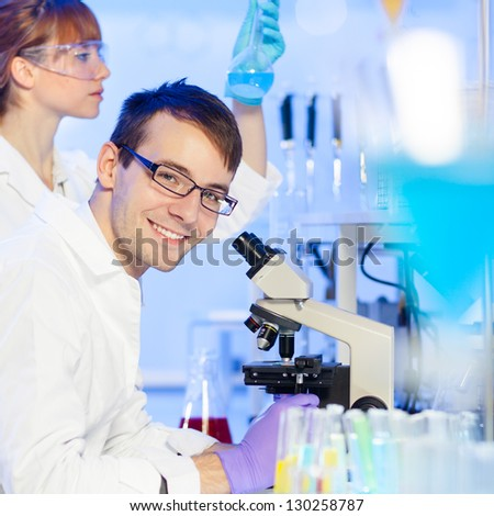 Portrait of a young researcher microscoping in the life science (forensics, microbiology, biochemistry, genetics, oncology..)laboratory. Assistant scientist examining blue liquid solution in the back. - stock photo