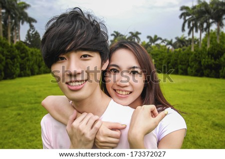 Portrait of a young romantic couple embracing each other on campus - stock photo