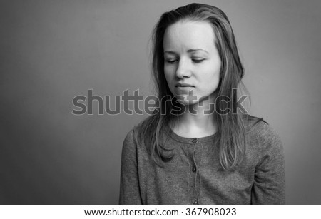 Portrait of a young sad woman, looking down, black and white image - stock photo