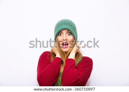 Portrait of a young scared woman.Funky girl in studio. .Shocked Girl.Beautiful Blonde woman looking surprised scared - funny. Isolated on white background.Wearing green hat ,scarf,sweater. - stock photo