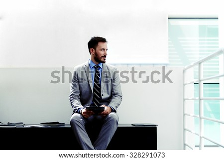 Portrait of a young serious men entrepreneur dressed in luxury clothes sitting with touch pad in office space, male managing director in suit thinking about something while work on digital tablet  - stock photo