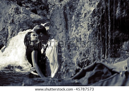 Portrait of a young sexy couple drinking a tea and making love on waterfall - stock photo