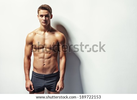 Portrait of a young sexy muscular man in underwear against white wall with copy space - stock photo