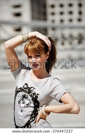 Portrait of a young sexy woman looking at the camera in a hot sunny day in urban background. Make up, short dress, fashion accessorizes.  - stock photo