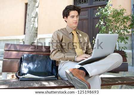 Portrait of a young smart businessman sitting on a wooden bench in the city and using his laptop computer, outdoors. - stock photo