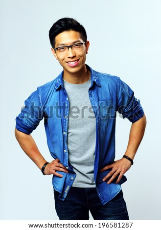 Portrait of a young smiling asian man on gray background - stock photo