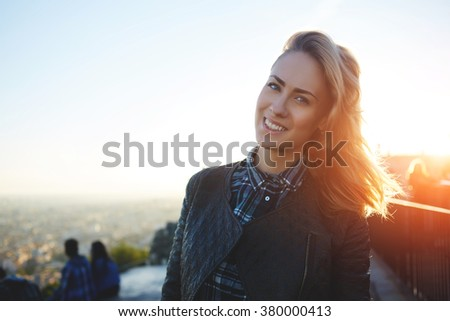 Portrait of a young smiling beautiful woman looking at camera while standing against sky and city landscape, gorgeous happy female posing while relaxing outdoors during her long-awaited spring weekend - stock photo