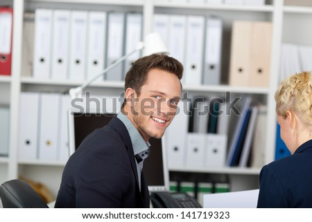Portrait of a young smiling businessman in meeting at office desk - stock photo