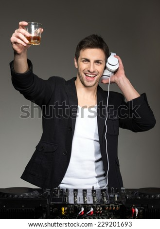 Portrait of a young smiling DJ standing at the mixer on a dark background. - stock photo