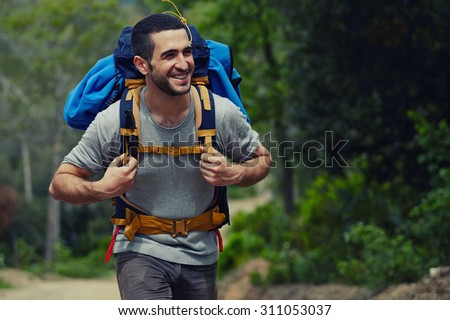 Portrait of a young smiling wanderer man with backpack goes on up the road with copy space, happy hiker walking lonely in mountains at summer day, traveler enjoying his recreation time in nature - stock photo