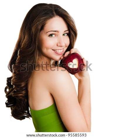 portrait of a young smiling woman holding red apple with heart shape - stock photo