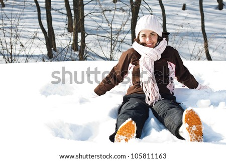 Portrait of a young smiling woman in snowy winter forest, wearing sporty winter clothes, sitting in the snow with legs stretched - stock photo