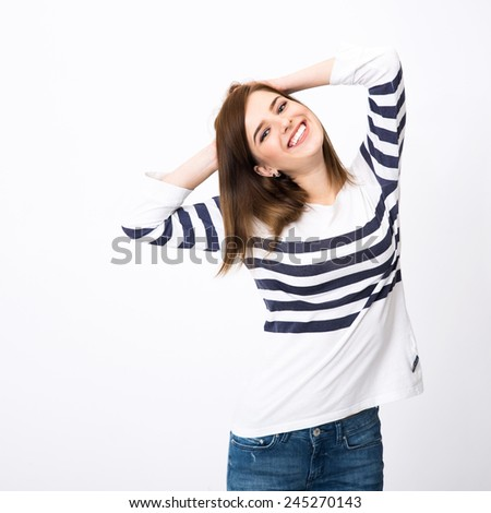 Portrait of a young smiling woman standing over gray background - stock photo