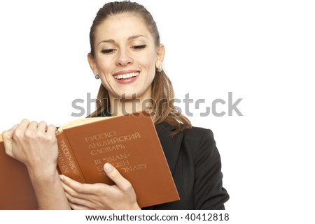 Portrait of a young smiling woman with english-russian dictionary. Isolated over white background - stock photo