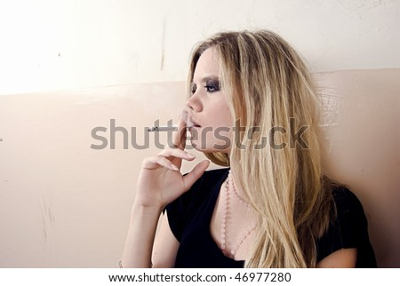 Portrait of a young smoking woman - stock photo