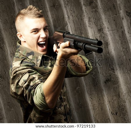 portrait of a young soldier aiming with a shotgun against a wooden wall - stock photo