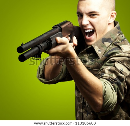 portrait of a young soldier aiming with shotgun against a green background - stock photo
