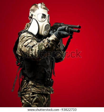 portrait of a young soldier with a gas mask aiming with a shotgun - stock photo