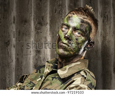 portrait of a young soldier with a jungle camouflage paint against a grunge background - stock photo