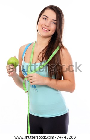 Portrait of a young sport woman holding apple and measuring tape over white background - stock photo