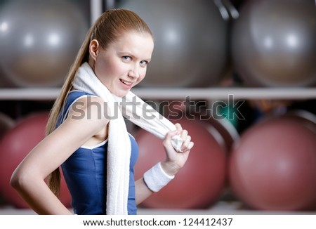 Portrait of a young sportive girl in tracksuit with white towel against a great variety of colorful balls - stock photo