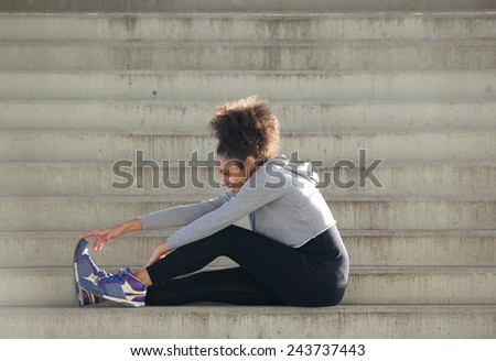 Portrait of a young sports woman sitting on stairs stretching leg muscles - stock photo