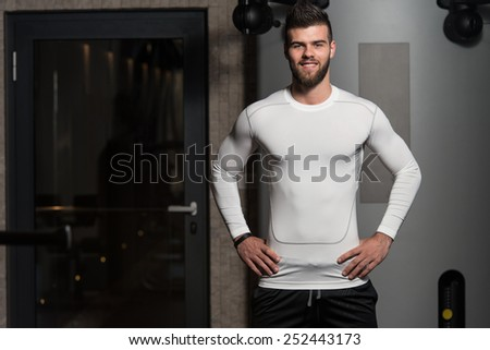 Portrait Of A Young Sporty Man In The Modern Gym With Exercise Equipment - stock photo