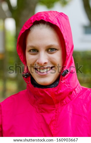 Portrait of a young, sporty woman in a rain jacket - stock photo