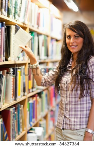 Portrait of a young student choosing a book while looking at the camera - stock photo