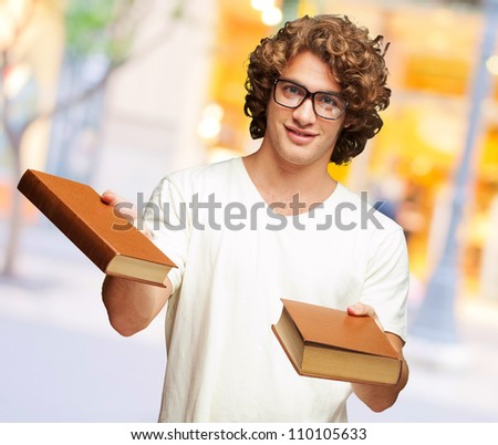 Portrait Of A Young Student Holding Books, Outdoor - stock photo