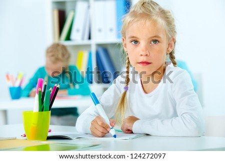 Portrait of a young student sitting at her desk in the classroom - stock photo