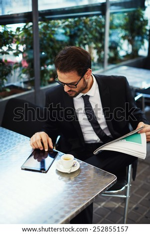 Portrait of a young successful businessman sitting in an coffee shop and using a digital tablet, business man having breakfast sitting on beautiful terrace with plants - stock photo