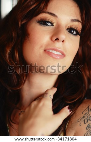 Portrait of a young tattooed brunette woman - stock photo