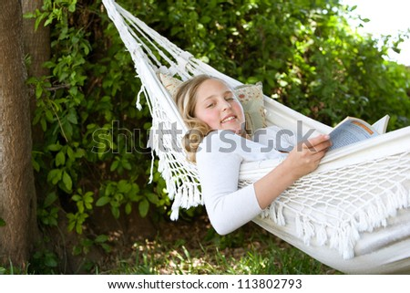 Portrait of a young teenage girl reading a book while laying down on a hammock in a garden, smiling. - stock photo